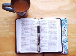 Open Bible with a pen and cup of coffee