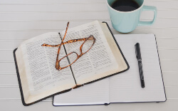 Open Bible with reading glasses, notebook, pen, and cup of coffee